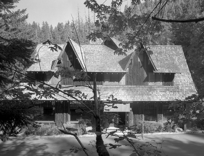 The Chateau at the Oregon Caves (1934) seen from street-level. The main entrance is under a canvas awning. Shed dormers broken up by gables.