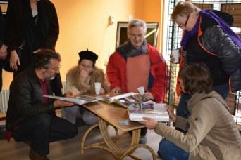 Quelques visiteurs penchés sur les albums de Thierry Vincent