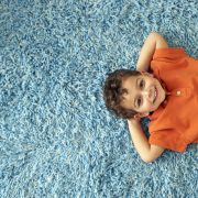 boy laying on blue carpet