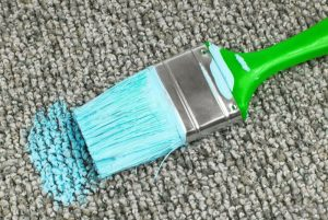 paint brush with blue paint on carpet