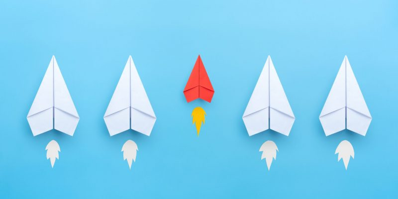 Small business concept with small red paper plane on blue background
