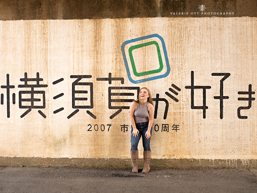 high school senior standing in front of a wall with japanese writing