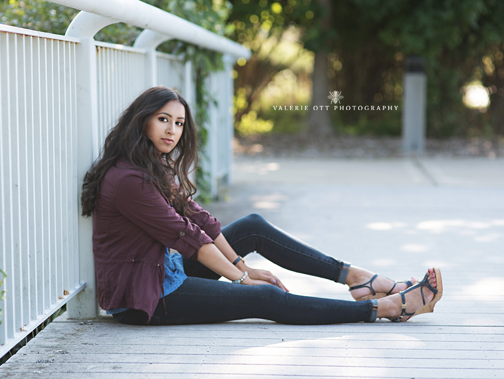 high school senior girl sitting on a bridge wearing a maroon jacket and jeans