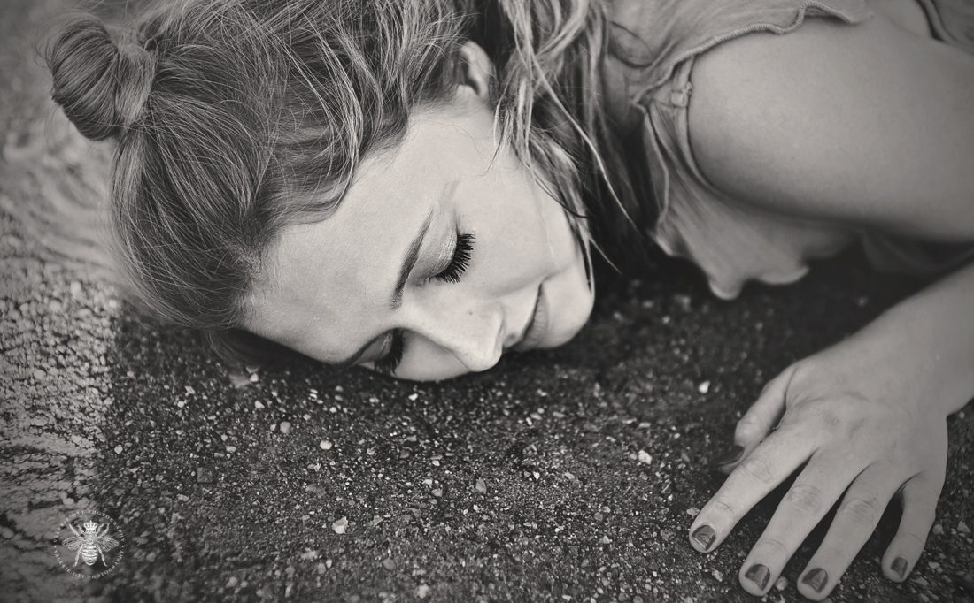 senior girl in the water with sand on her skin
