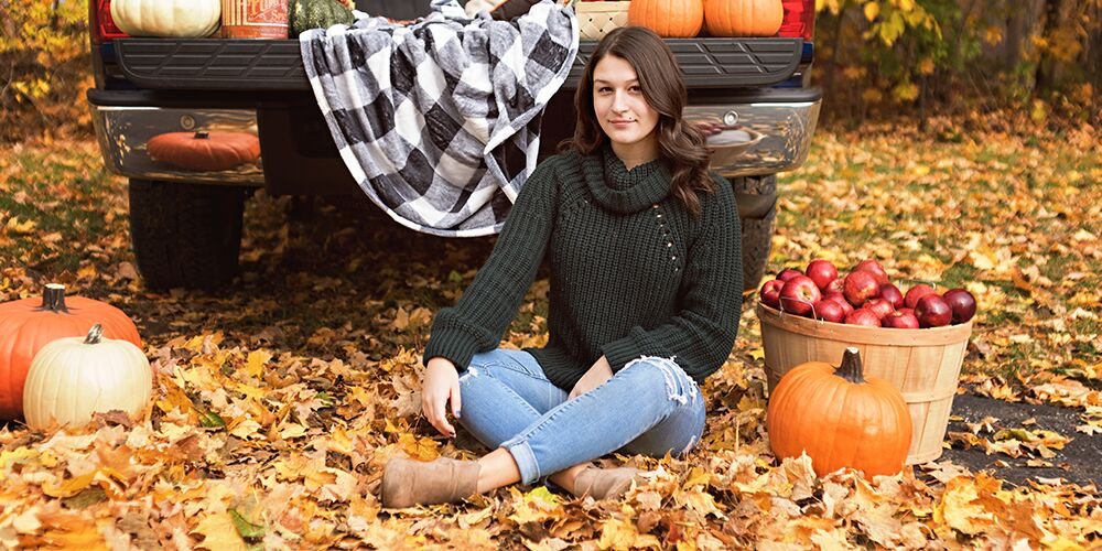 senior girl poses in fall by truck