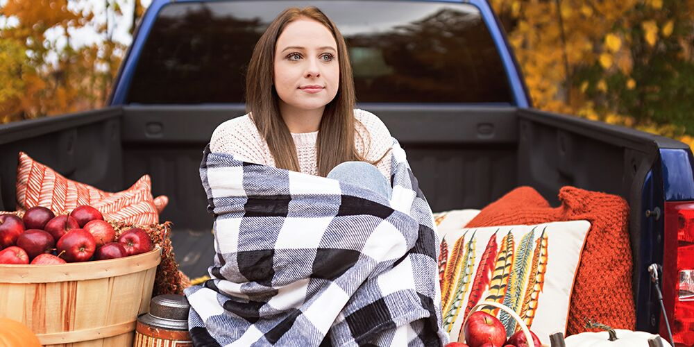 senior girl poses with checkered blanket in fall