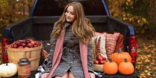 senior girl in coat and scarf sitting on truck in fall location