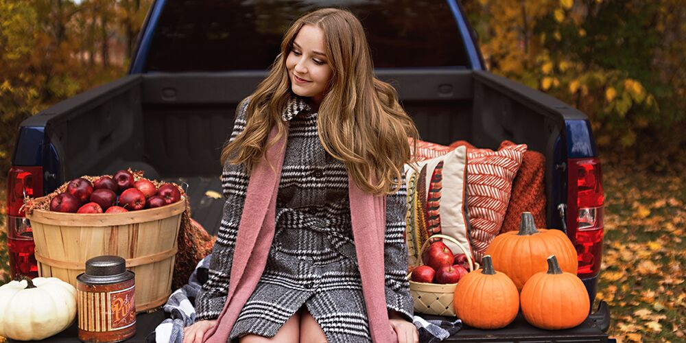 senior girl in coat and scarf sitting on truck