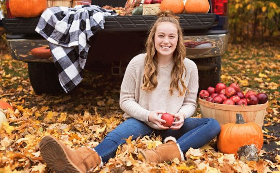 senior girl poses with apples in fall