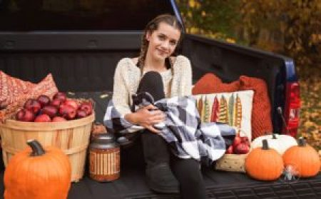 senior girl poses with checkered blanket on truck in fall