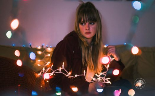 senior girl poses with twinkle lights