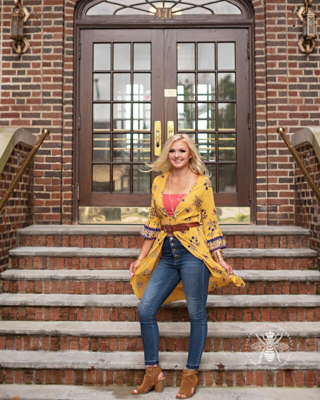 senior girl poses in yellow top on stairs