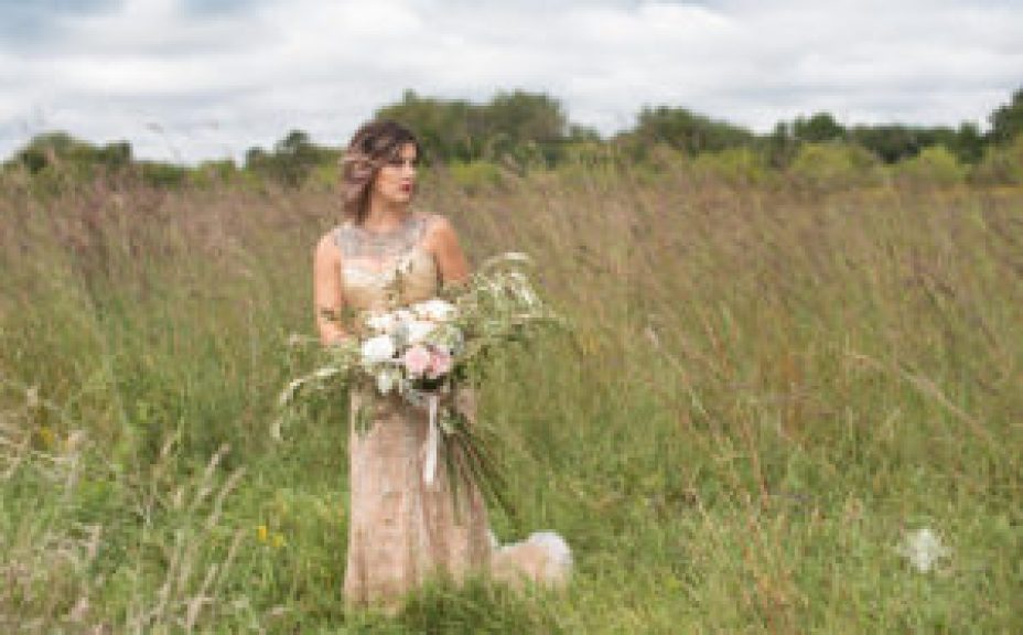 bride poses with bouquet of flowers in a field
