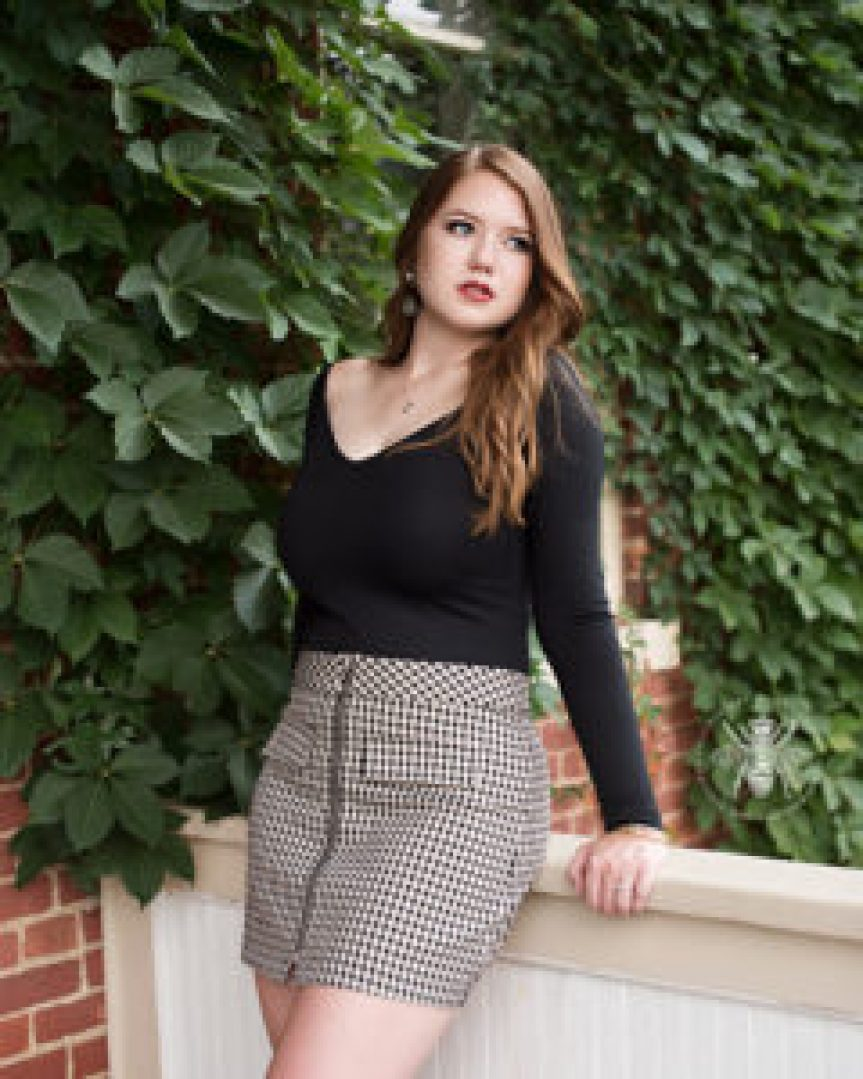 senior girl poses in black top and skirt in front of greenery