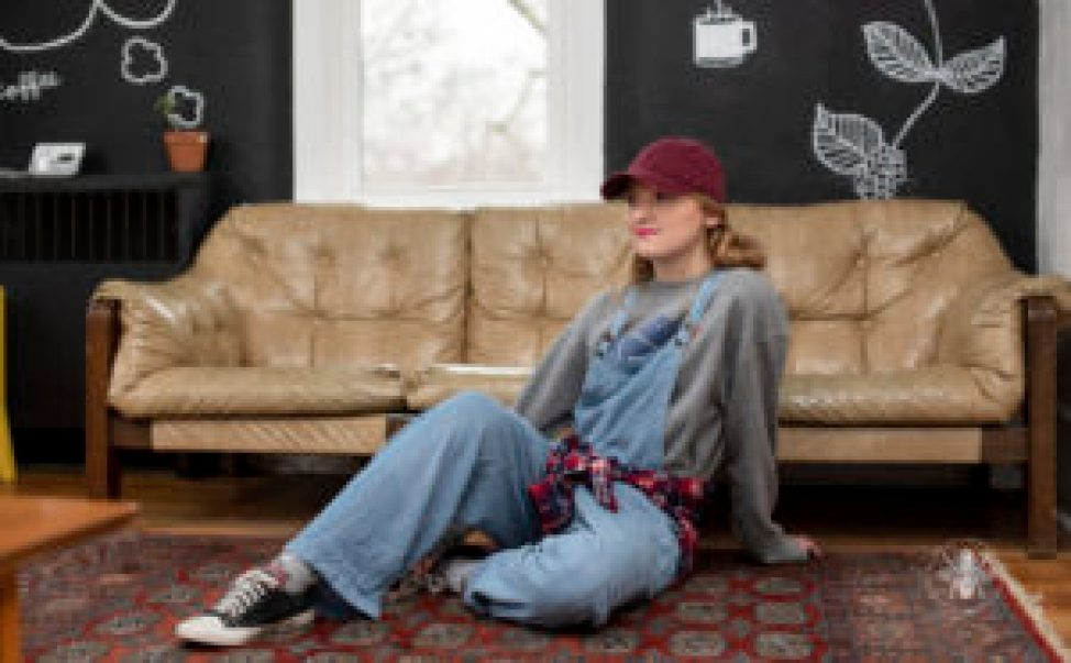 Senior girl poses in overalls, flannel, and red baseball cap in coffee shop