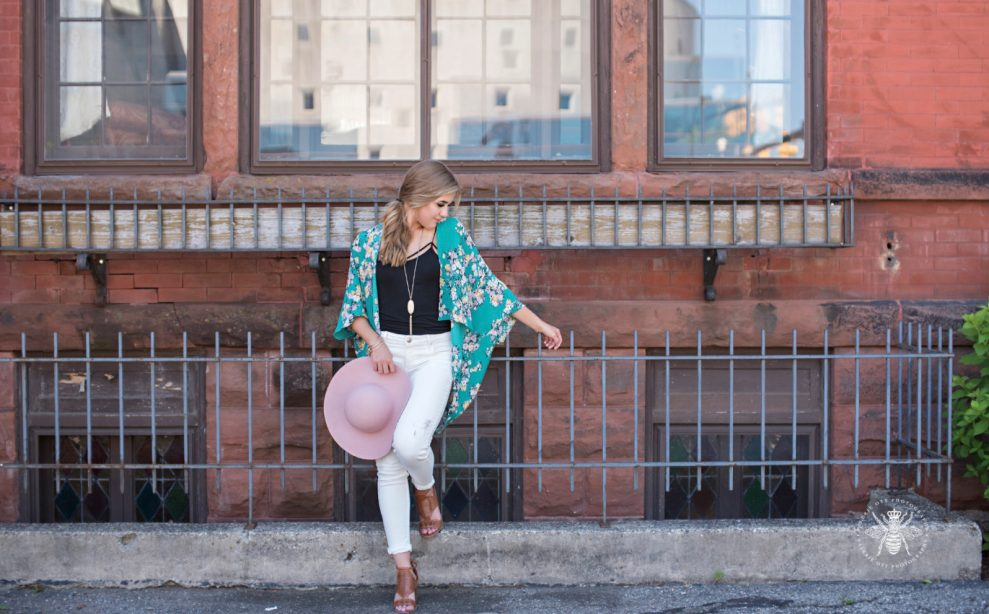 senior girl poses holding pink hat, wearing green floral shawl, long necklace, black tank top, and white jeans.