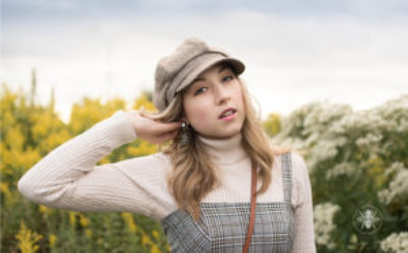 senior girl poses in hat and overalls in field korean style