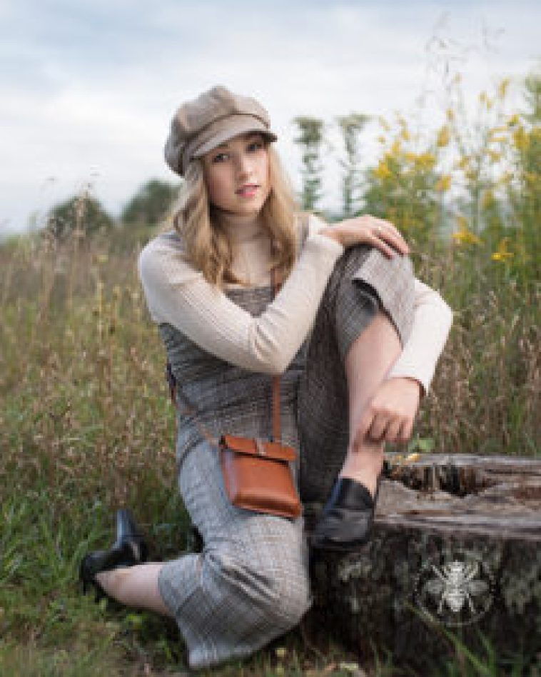 senior girl poses in hat and overalls korean style