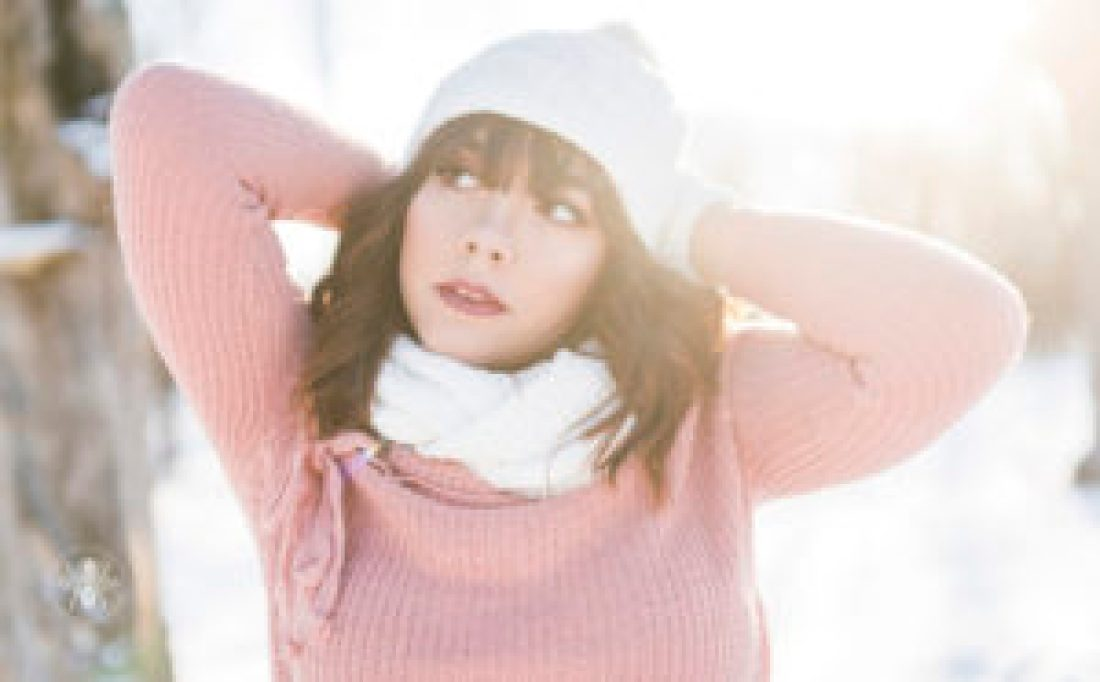 senior girl poses in pink sweater, white hat, scarf and gloves in winter