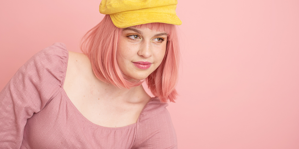 senior girl poses in front of pastel pink background wearing a pastel pink wig and a yellow hat