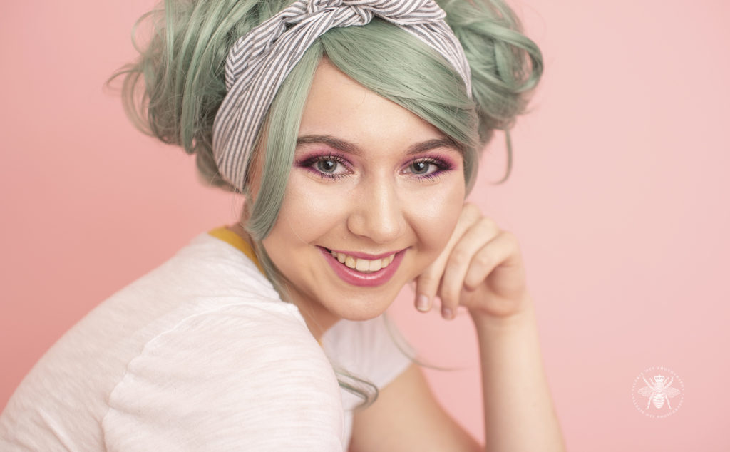 senior girl poses in front of pastel pink background with green hair