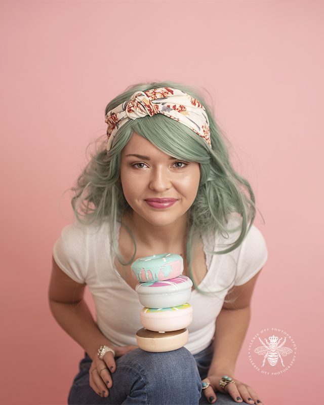 senior girl poses with foam donut and pastel green colored hair in front of a pink background