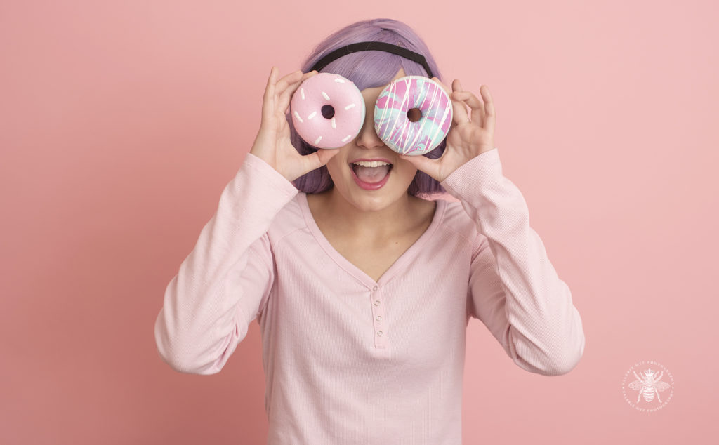 senior girl poses with foam donut and pastel purple colored hair in front of a pink background