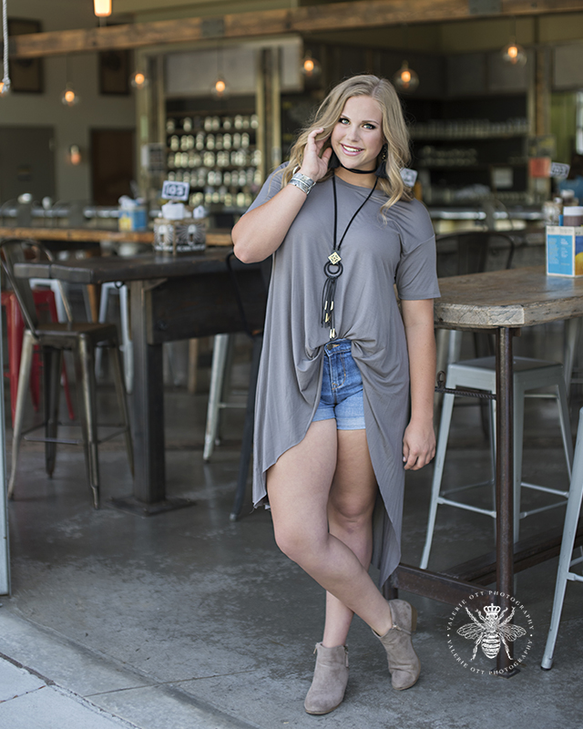 senior girl poses in high-low top with shorts