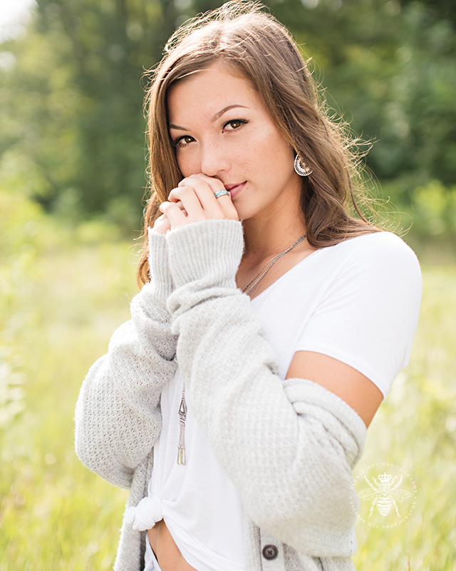 senior girl wears cardigan and poses in field