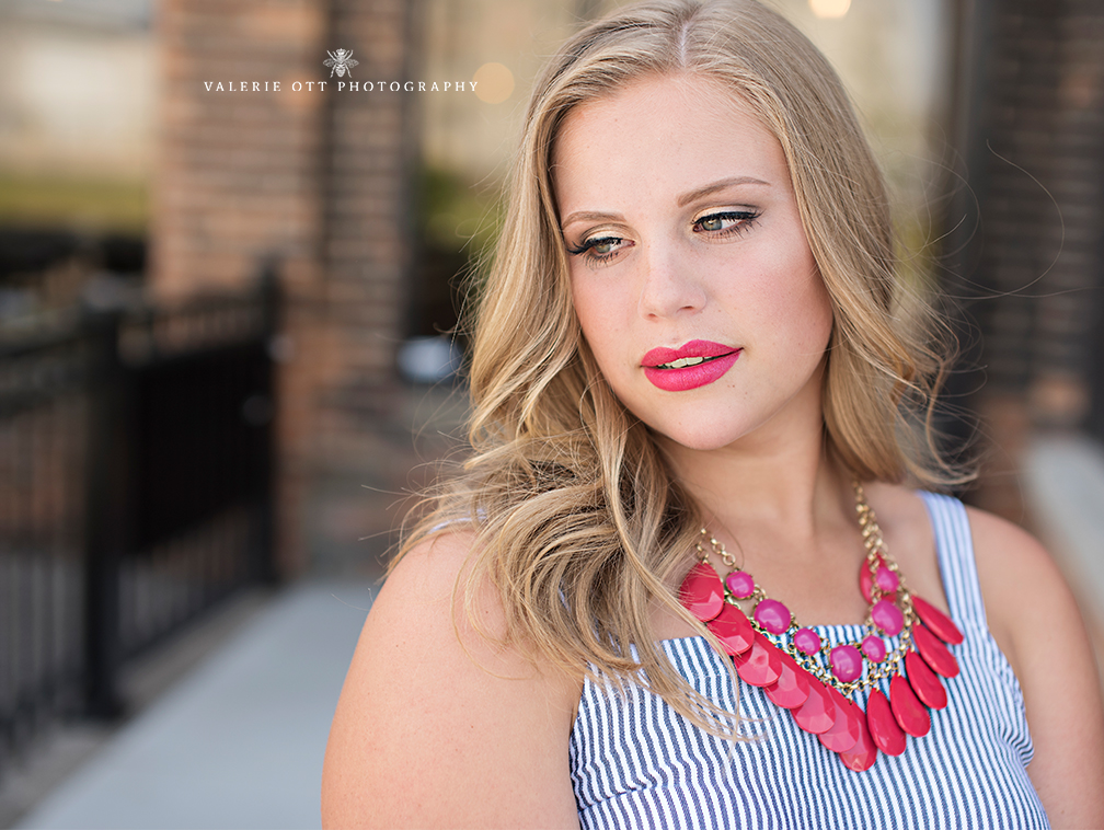 senior girl wears pink necklace and matching pink lip