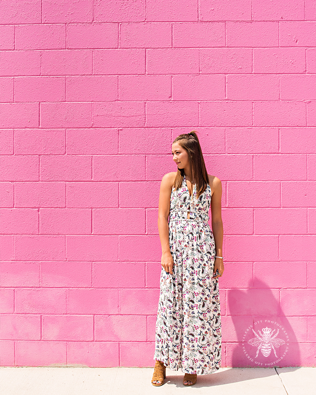 senior girl poses in front of pink wall