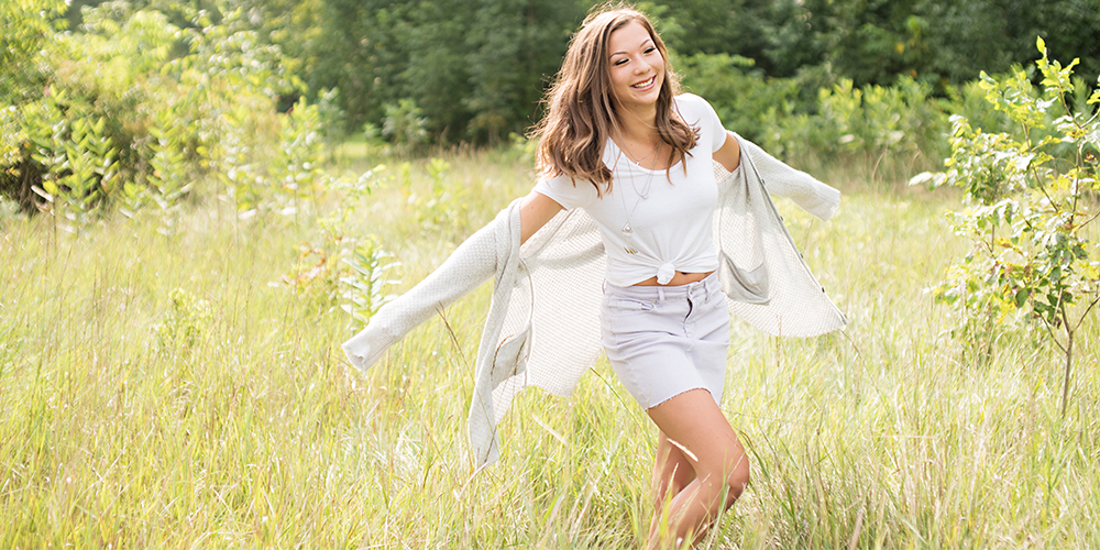 senior girl wears white skirt and cardigan and runs through field