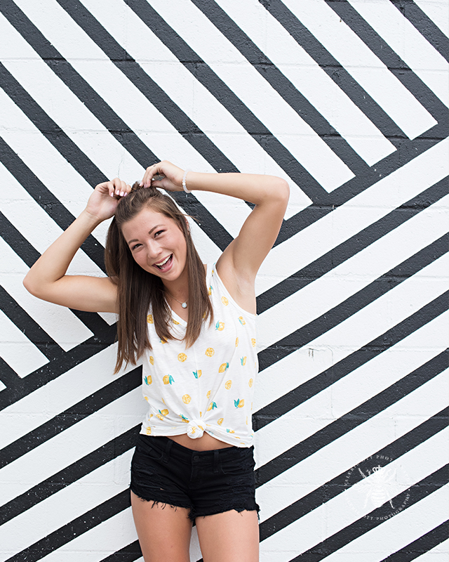 senior girl poses in front of black and white striped wall