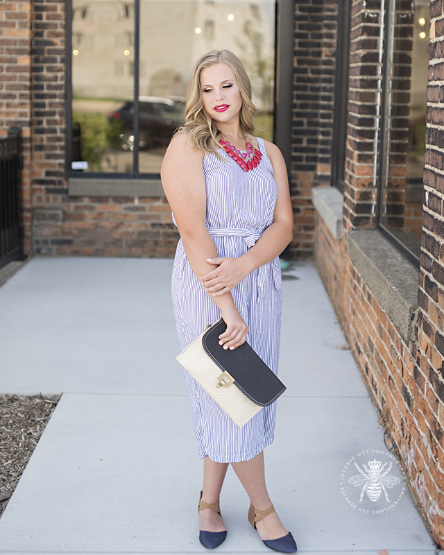senior girl poses in blue striped jumpsuit and pink necklace with a matching pink lip