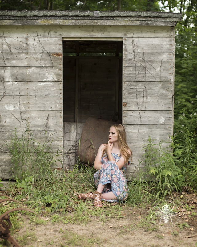 senior girl poses in front of a vintage barn