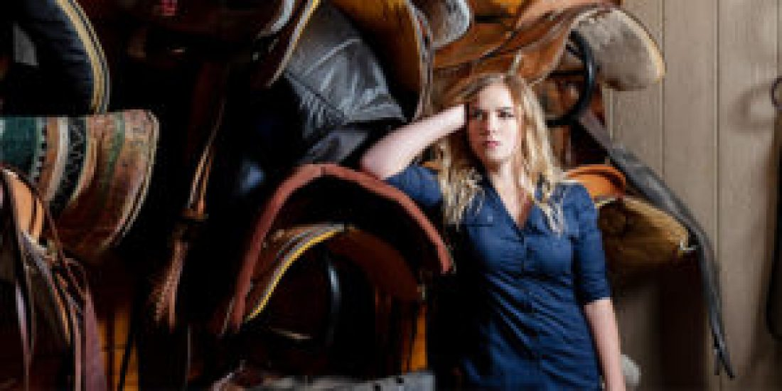 senior girl poses with saddles in stable