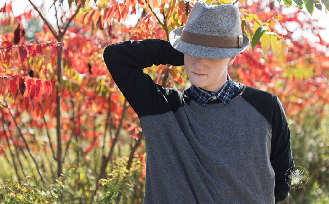 senior guy poses in front of fall colors wearing fedora