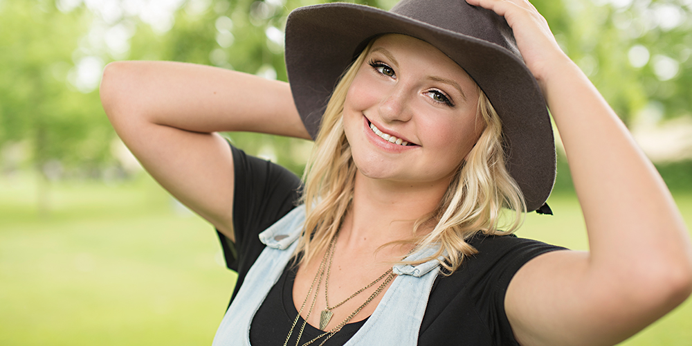 senior girl poses wearing hat in a field