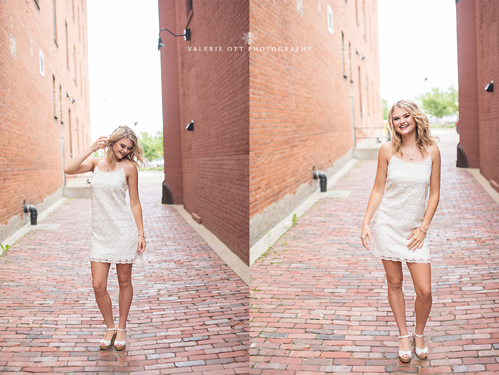 senior girl wears a little white dress and dances in the street