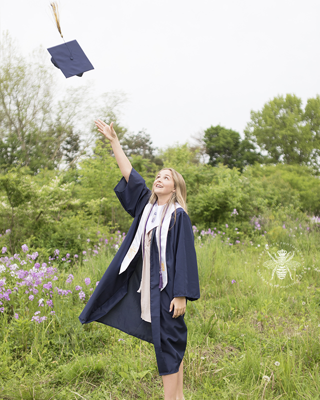 West Michigan High School graduate poses for a cap and gown session in a field. She throws her cap up in the air.