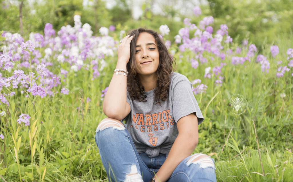 West Michigan high school graduate poses in a field wearing a college t shirt