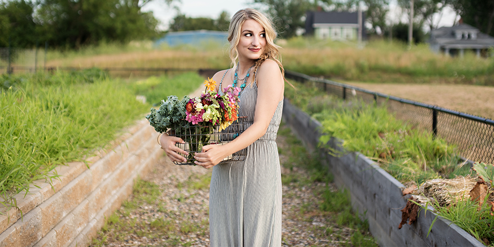 senior girl poses with bouquet of flowers, she wears a long black and white striped dress and blue necklace
