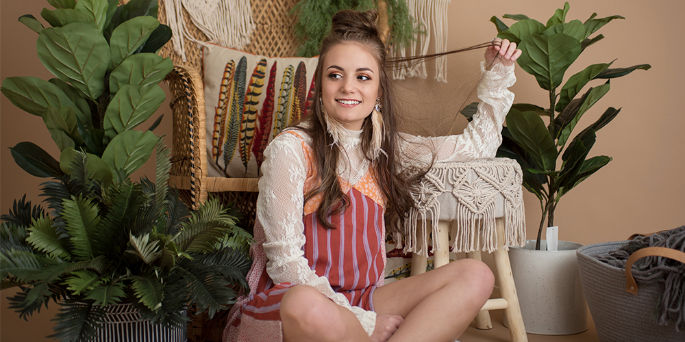 Mattawan senior girl poses in a studio with a vintage background with plants. She wears her hair half up, feather earrings, an orange, red and purple striped sundress layered over a white lace high neck top.
