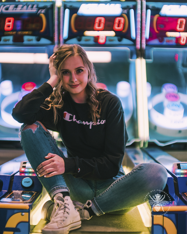 West Michigan senior girl poses by arcade games in Revel and Roll. She wears ripped jeans, converse, and a Champion sweatshirt.