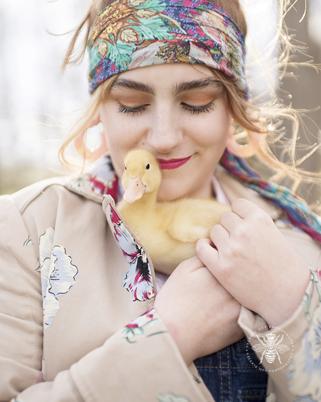 West Michigan senior poses with baby ducks in a field. She wears her hair in a bun with a floral hair scarf and floral jacket.