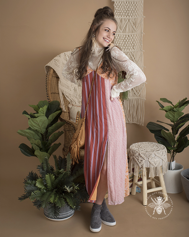 Mattawan senior girl poses in a studio with a vintage background with plants. She wears her hair half up, feather earrings, an orange, red and purple striped sundress layered over a white lace high neck top, and she wears gray wedge sneakers, and she wears a brown crossbody bag with fringe.