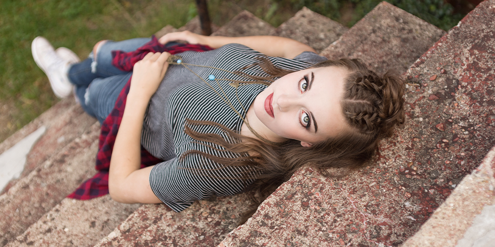 senior girl poses laying on the steps. She looks up at the camera with her blue eyes. She wears a black and white striped top, a turquoise layered necklace, jeans, and a red flannel tied around her waist.