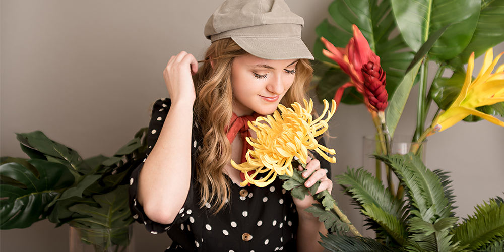 West Michigan senior session. Senior poses with red and yellow flowers in front of gray background. She wears a rust colored scarf around her neck, a tan hat, and a black and white polka dot top.