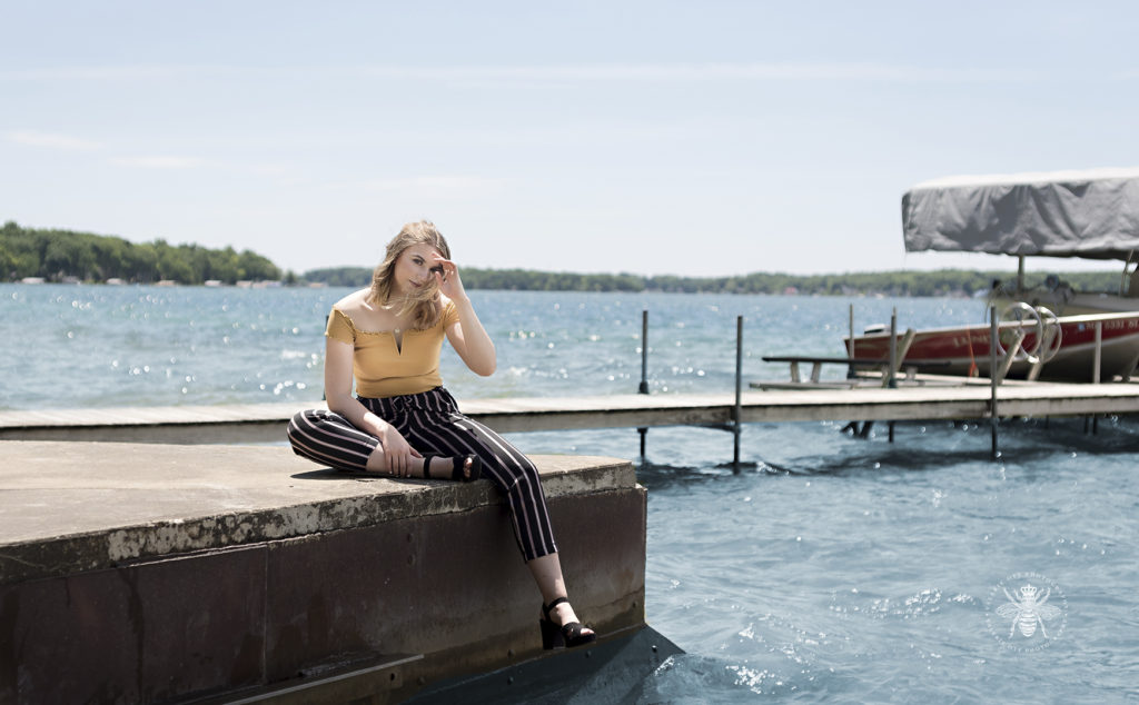 gull lake senior girl chose meaningful places and poses by the water near a dock. She wears black striped pants, a yellow of the shoulder top, and a black heels. She runs her fingers through her hair and sits.