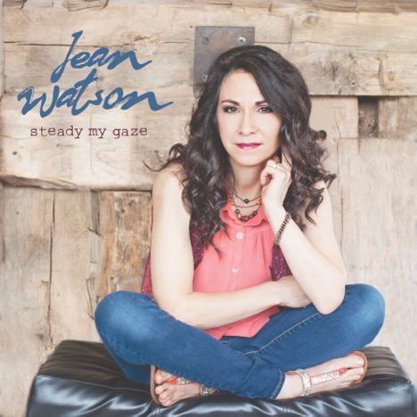 Album cover for Irish worship singer. She poses sitting in front of a wood wall. Text reads: Jean Watson, steady my gaze